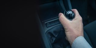 Man hand holding gear shift on his auto. On black background royalty free stock photos