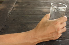 Man hand holding a glass of water. On wood background Royalty Free Stock Photo