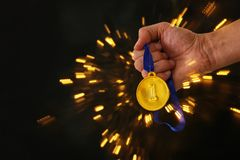 Man hand holding gold medal against black background. Award and victory concept. Man hand holding gold medal against black background. Award and victory concept Royalty Free Stock Images