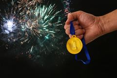 Man hand holding gold medal against black background with fireworks overlay. Award and victory concept. Man hand holding gold medal against black background Royalty Free Stock Images