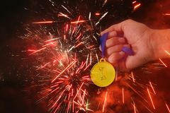 Man hand holding gold medal against black background with fireworks overlay. Award and victory concept. Man hand holding gold medal against black background Royalty Free Stock Image