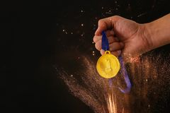 Man hand holding gold medal against black background with fireworks overlay. Award and victory concept. Man hand holding gold medal against black background Stock Image