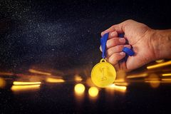 Man hand holding gold medal against black background with glitter overlay. Award and victory concept. Man hand holding gold medal against black background with Stock Image