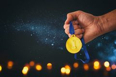 Man hand holding gold medal against black background with glitter overlay. Award and victory concept. Man hand holding gold medal against black background with Royalty Free Stock Images