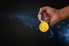 Man hand holding gold medal against black background with glitter overlay. Award and victory concept. Man hand holding gold medal against black background with Royalty Free Stock Image