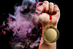 Man hand holding a gold medal royalty free stock image
