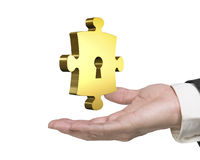 Man hand holding golden puzzle piece with keyhole Stock Photos
