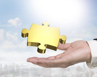 Man hand holding golden puzzle piece. Man`s hand holding one golden puzzle piece Royalty Free Stock Image