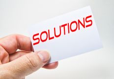 Man hand holding a gray billboard with solution word written in it on a white background stock image