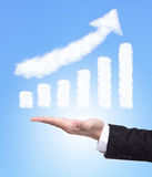 Man hand holding growth graph. Business man hand holding a growth graph ( made by cloud ) in the air with blue sky, finance and business concept Royalty Free Stock Image