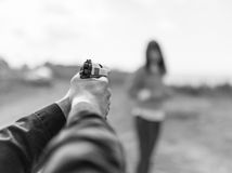 Man hand holding gun aim to woman. Selective focus with shallow depth of field. Black and white toning stock image