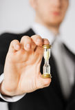 Man hand holding hourglass. Close up of man hand holding hourglass Royalty Free Stock Photo