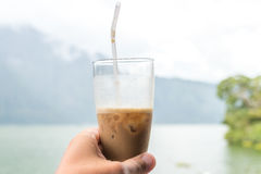Man hand holding Iced coffee or caffe latte on a mountain background. Bali island. Royalty Free Stock Photography