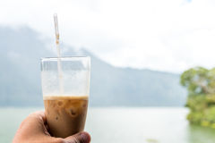 Man hand holding Iced coffee or caffe latte on a mountain background. Bali island. Royalty Free Stock Photo