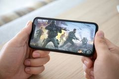 Free Man Hand Holding IPhone 11 Game Call Of Duty Mobile Royalty Free Stock Images - 160537339