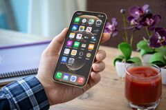 Free Man Hand Holding IPhone 12 Pro Max Gold IOS 14 Stock Images - 208396884