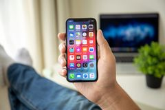 Man hand holding iPhone X with home screen IOS. Alushta, Russia - July 29, 2018: Man hand holding iPhone X with home screen IOS. iPhone 10 was created and stock image