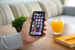 Man hand holding iPhone X with home screen IOS royalty free stock image