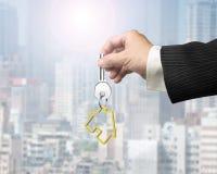 Man hand holding key with house shape keyring Royalty Free Stock Photos
