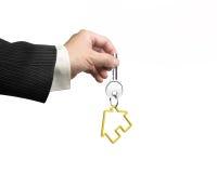 Man hand holding key with house shape keyring Stock Image