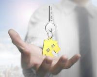 Man hand holding key with house shape keyring Stock Photo