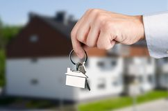 Man hand holding keys with to new house Royalty Free Stock Photography