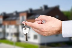 Man hand holding keys with to new house Stock Image