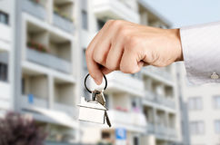Man hand holding keys with to new house Royalty Free Stock Images
