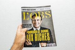 Man hand holding l`Obs magazine with Emmanuel macron on cover stock images
