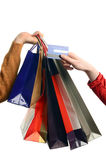 Man hand holding many shopping bags, female hand holding a credit card. Royalty Free Stock Photography