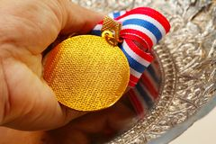 Man hand in holding medal with fabric neck holder ribbon. Man hand in holding medal with fabric neck holder ribbon scene Royalty Free Stock Photography