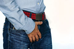 Man hand holding on middle crotch of trousers. On white background with copy space Stock Image