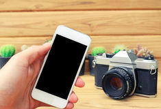 Man hand holding mobile phone blank screen with camera cactus an Stock Photo