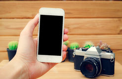 Man hand holding mobile phone blank screen with camera cactus an Royalty Free Stock Photo