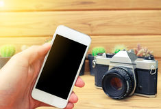 Man hand holding mobile phone blank screen with camera cactus and wood background. Stock Image