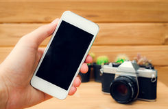 Man hand holding mobile phone blank screen with camera cactus and wood background. Royalty Free Stock Image
