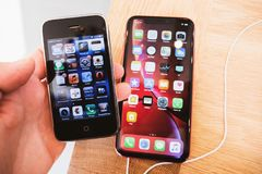 Free Man Hand Holding New IPhone XR Smartphone Telephone Comparing 3gs Royalty Free Stock Images - 154640109