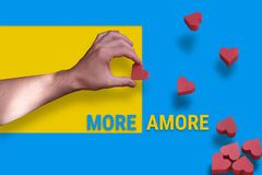 Male hand holding a heart on a yellow-blue background. Many hearts like likes fall down with text more amore royalty free stock image
