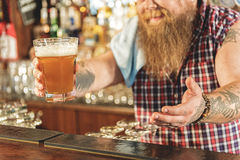 Man hand holding out drinks in pub Stock Image