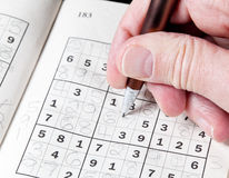 Man hand holding pencil on sudoku puzzle Royalty Free Stock Photography