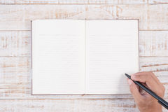Man hand holding pencil and writing notebook  on wood table for Stock Images
