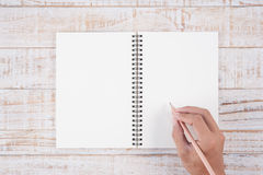 Man hand holding pencil and writing notebook  on wood table for Stock Photos