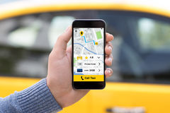 Man hand holding phone with app call taxi on screen. Man hand holding phone with app call taxi screen on background of yellow car Stock Images