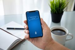 Man hand holding phone with app personal assistant on screen. Over table in the office stock photos