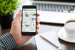 Man hand holding phone with world news site on screen Royalty Free Stock Images