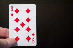 Man hand holding playing cards nine of diamonds isolated on black background with copyspace abstract. Close up shot Stock Photography