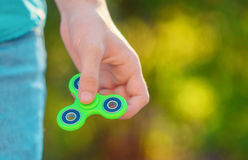 Man hand holding  popular antistress gadget fidget spinner. Man playing with green spinner outdoors  on the bright bokeh. Shallow DOF Stock Photo