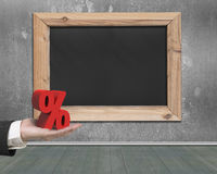 Man hand holding red percentage sign with blank blackboard Royalty Free Stock Photo