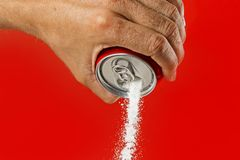 Man hand holding refresh drink can pouring sugar stream in sweet and calories content of soda and energy drinks Royalty Free Stock Images