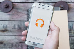 A man hand holding screen shot of google play music. Stock Photo